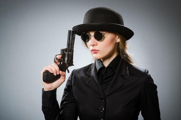 Mujer espía con arma contra gris.