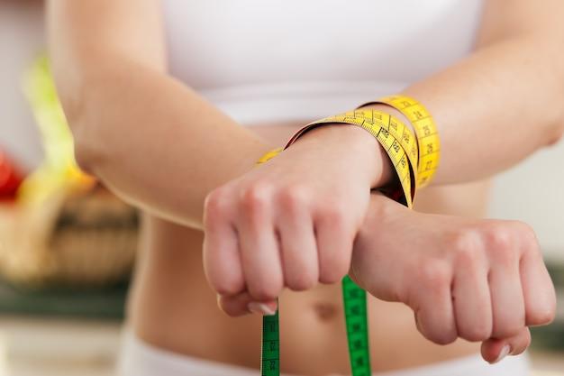 Mujer esposada por una cinta métrica - símbolo del trastorno alimentario