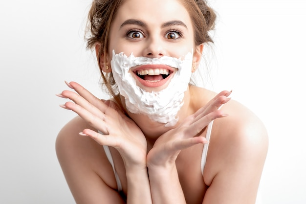 Mujer con espuma de afeitar en la cara