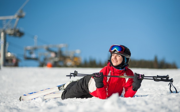 Mujer esquiador con esquí en winer resort en día soleado