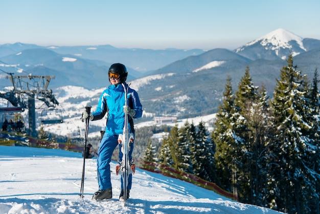 Mujer esquiador en pendiente en la estación de esquí en invierno