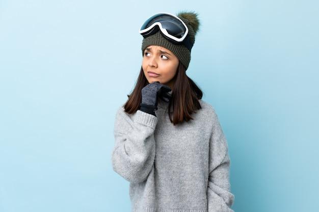 Mujer de esquiador de raza mixta con gafas de snowboard sobre espacio azul aislado con dudas y con expresión de la cara confusa