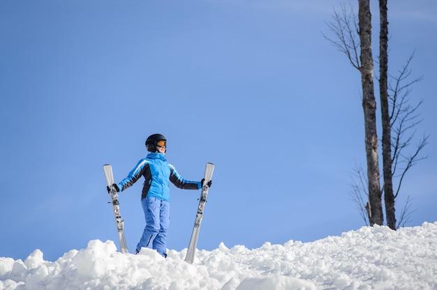 Mujer esquiadora en un día soleado. mujer sostiene sus esquís