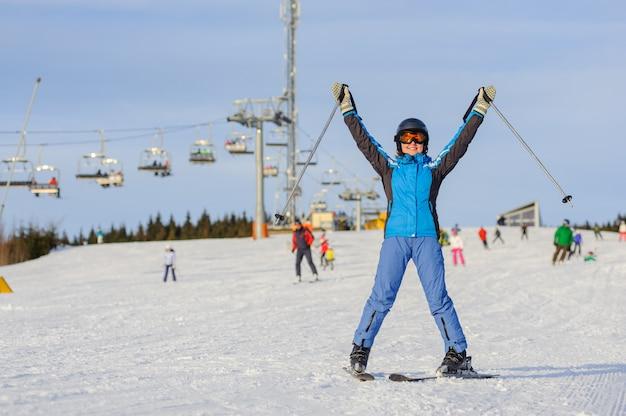 Mujer esquiadora esquiando cuesta abajo en la estación de esquí contra el remonte