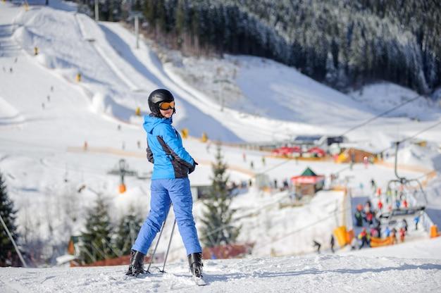 Mujer esquiadora en una pista de esquí en un día soleado