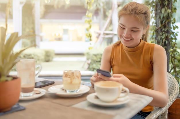La mujer estaba jugando un teléfono móvil en la cafetería