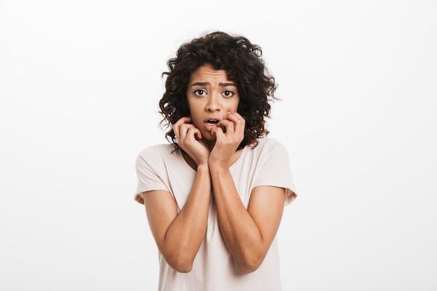 Mujer estadounidense de 20 años en camiseta básica mordiéndose las uñas y sintiéndose asustada y asustada, aislado sobre la pared blanca