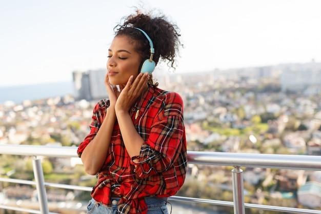 Mujer estadounidense pensativa con piel oscura posando con auriculares en la azotea. fondo de paisaje urbano