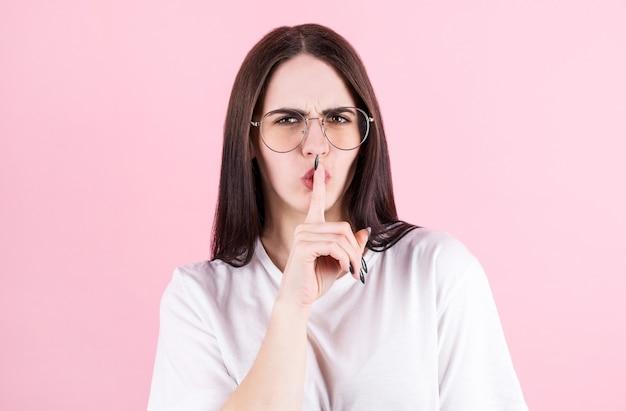 Una mujer estadounidense presiona el dedo índice contra los labios, pide silencio, dice información muy privada, usa un chaleco amarillo informal, posa en el estudio, dice silencio o silencio