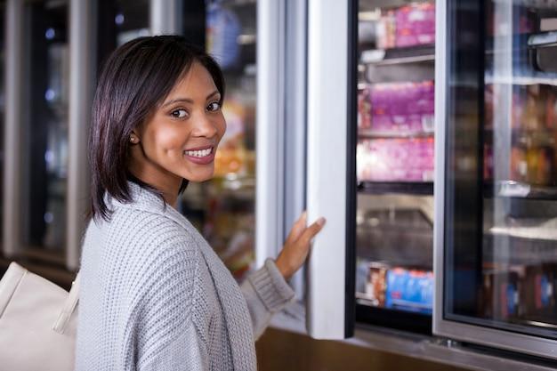 Mujer estar de pie, cerca, refrigerador