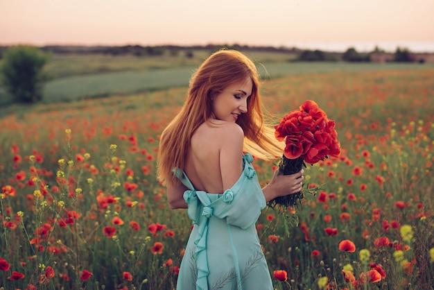 Mujer estar de pie, en, florecimiento, campo de amapolas
