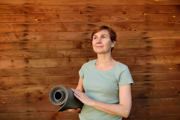 Mujer con una estera de yoga en el fondo de pared de madera