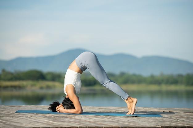 Mujer en una estera de yoga para relajarse en el parque en el lago de la montaña. atractiva chica deportiva en ropa deportiva. chica deportiva haciendo ejercicio. estilo de vida deportivo saludable. joven atlética haciendo ejercicio físico.