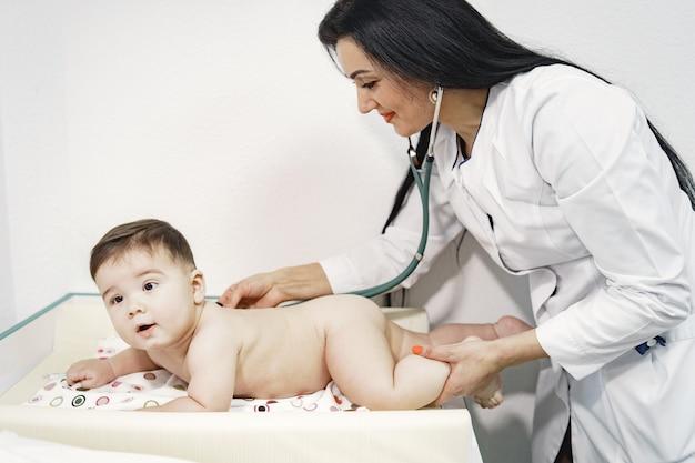 Mujer con estetoscopio. bebé en pañal. bebé acostado boca abajo.