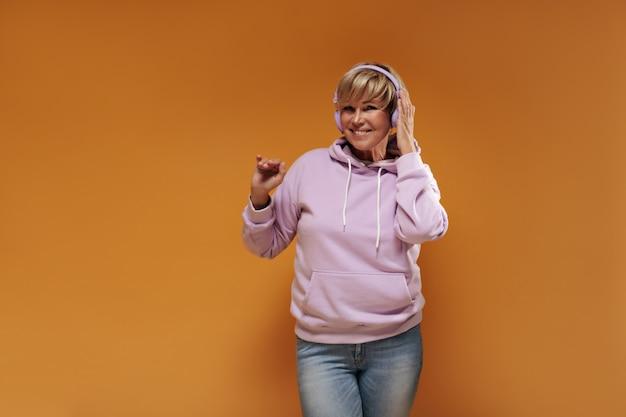 Mujer con estilo alegre con peinado corto y modernos auriculares púrpuras en jeans y sudadera con capucha de moda sonriendo y escuchando música.