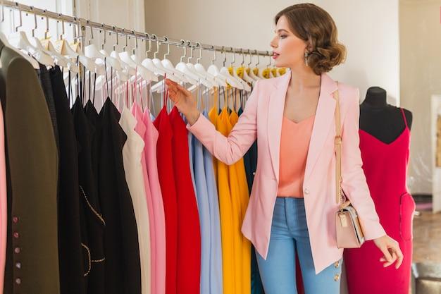Mujer con estilo atractivo elegir ropa en tienda de ropa