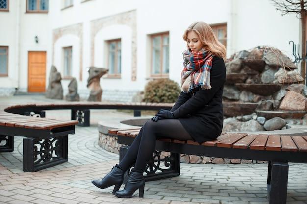 Mujer con estilo atractivo joven en abrigo de invierno de moda en guantes negros con una bufanda de lana en zapatos negros con tacones sentado en la ciudad en un banco de madera vintage en un día de otoño. niña bonita