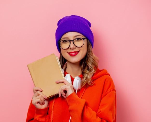 Mujer de estilo con auriculares y libros en pared rosa