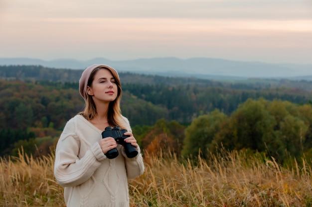 Mujer de estilo con binoculares en el campo con montañas