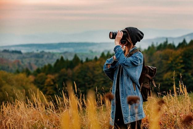 Mujer de estilo con cámara de fotos y mochila en el campo con montañas