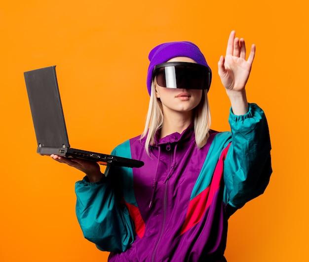 Mujer de estilo en chándal de los años 90 y gafas de realidad virtual con cuaderno en naranja