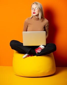 Mujer con estilo hipster con cuaderno sentado en silla de frijol amarillo en pared naranja