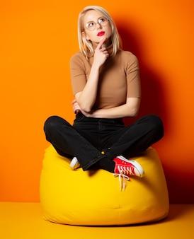 Mujer de estilo hipster sentada en la silla de frijol amarillo en la pared naranja