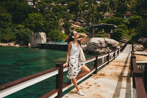 Mujer con estilo joven de pie en el muelle, caminar, escuchar música en auriculares, ropa de verano, falda blanca, bolso, agua azul, fondo de paisaje, laguna tropical, vacaciones, viajar en asia