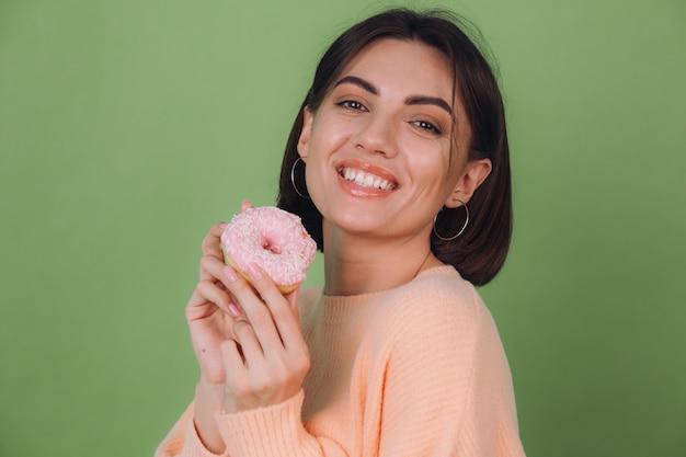 Mujer con estilo joven en suéter de melocotón casual aislado en la pared verde oliva con espacio de copia feliz rosquilla rosa