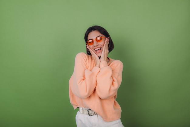 Mujer con estilo joven en suéter de melocotón casual y gafas naranjas aisladas en la pared de olivo verde risa sonriente positiva feliz alrededor de espacio de copia