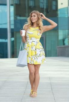 Mujer con estilo joven tomando café para ir en una calle de la ciudad