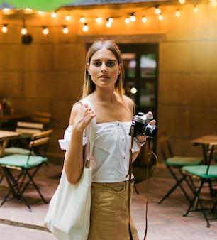 Mujer con estilo de moda en ropa de moda y gafas de sol posando al aire libre