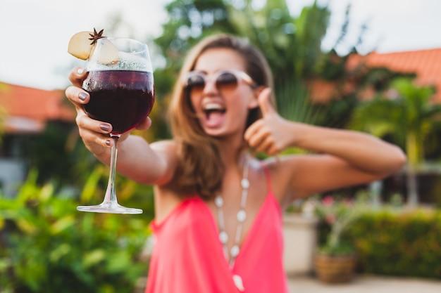 Mujer con estilo sexy en traje de fiesta de moda en vacaciones de verano con copa de cóctel divirtiéndose en la piscina