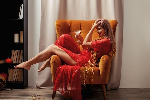 Mujer de estilo en vestido está sentada en un sillón clásico con vidrio