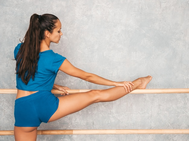 Mujer estirando antes de entrenar cerca de la pared gris en estudio
