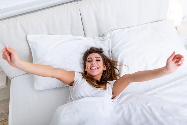 Mujer estirando en la cama con los brazos levantados. retrato de mujer encantadora atractiva disfrutando de mal tiempo después de dormir acostado debajo de la manta haciendo estiramientos manteniendo los ojos cerrados. buen dia vida salud