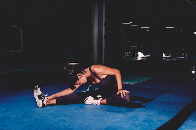 Mujer estirando en gimnasio