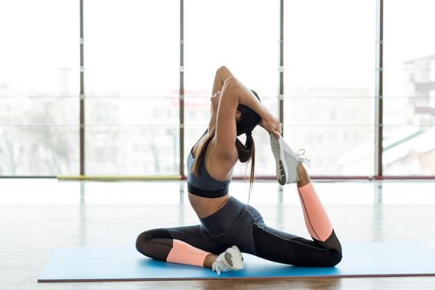 Mujer estirando y haciendo ejercicio en el gimnasio