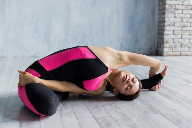 Mujer estirando la pierna con el brazo extendido