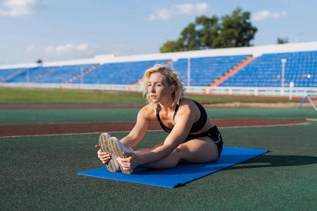 Mujer estirando sobre estera en el estadio