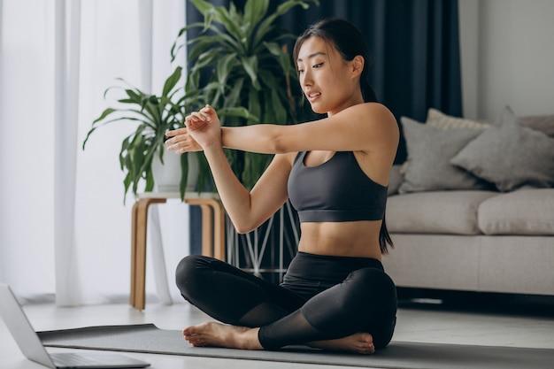 Mujer estirando sobre estera de yoga en casa