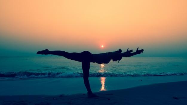 Mujer estirando su cuerpo en poses de yoga al atardecer en la playa