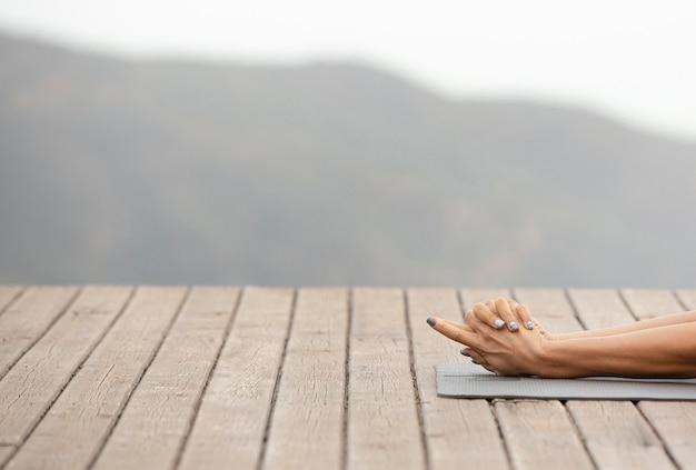 Mujer estirando sus brazos mientras hace yoga al aire libre con espacio de copia