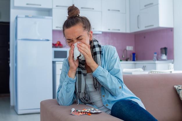 Mujer estornuda enferma en bufanda se resfrió. tratamiento de frío en casa