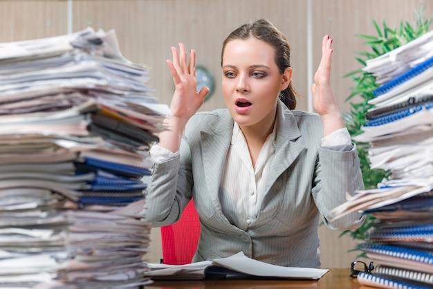 Mujer estresada por exceso de papeleo.