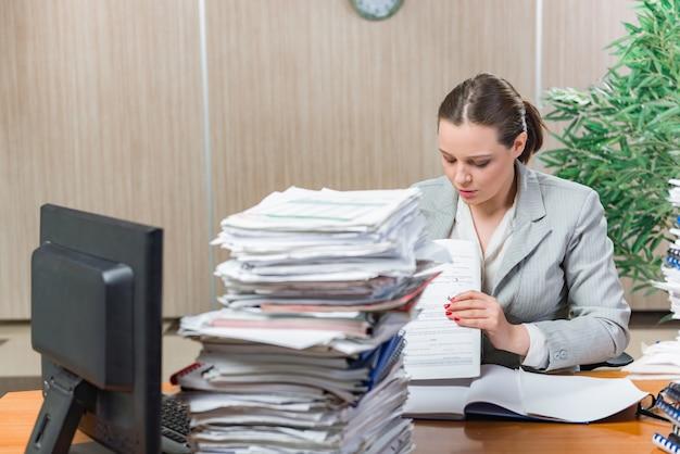 Mujer estresada por exceso de papeleo