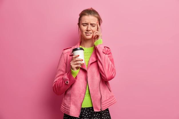 Mujer estresada con exceso de trabajo toca las sienes, tiene dolor de cabeza insoportable, bebe café para llevar, usa chaqueta rosa, cierra los ojos para aliviar el dolor, posa en interiores. gente, estilo de vida