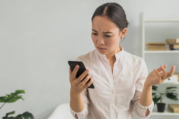 Mujer estresada en la oficina revisando el teléfono