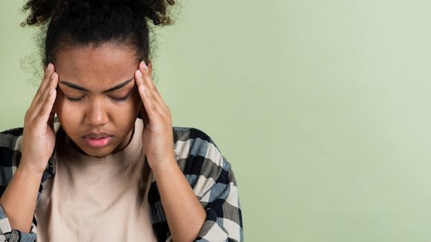 Mujer estresada que tiene dolor de cabeza