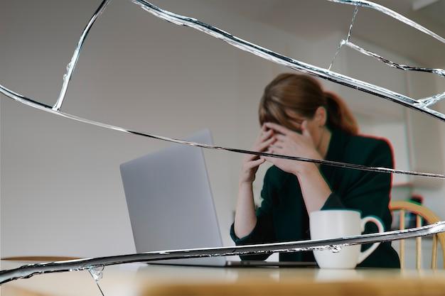Mujer estresada sentada frente a la computadora portátil con efecto de cristal agrietado